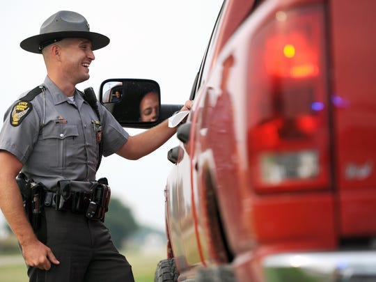 Ohio State Highway Trooper Sam Davis smiles at a comment made by a motorist during his patrol on Wednesday. Davis helped motorist with vehicle problems, issued cautions and handed out several tickets during his shift. With the upcoming holiday weekend an increase in traffic on the roads means an increased presence of troopers on the roadways as well.