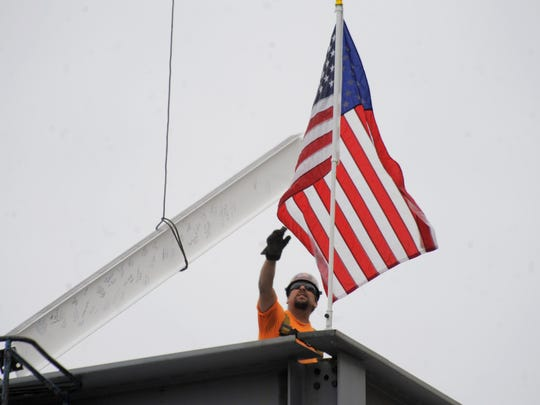 Construction worker Jason Wikaryasz on Tuesday guides the final steel beam into the two-story building.