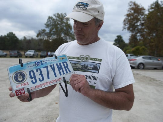 Dr. Emile DeVito with NJ Conservation Foundation holds up a license plate he found at a site in Wharton State Forest that he has been monitoring for endangered plant life. Environmental groups says damaging off-road vehicle use has become a major problem in the Pinelands National Reserve, especially in Wharton State Forest. Tuesday, October 13, 2015.