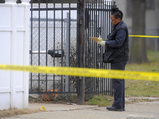 A Detroit police technician records information Wednesday after a fatal dog mauling near the corner of Baylis and the John C. Lodge Service Drive in Detroit.