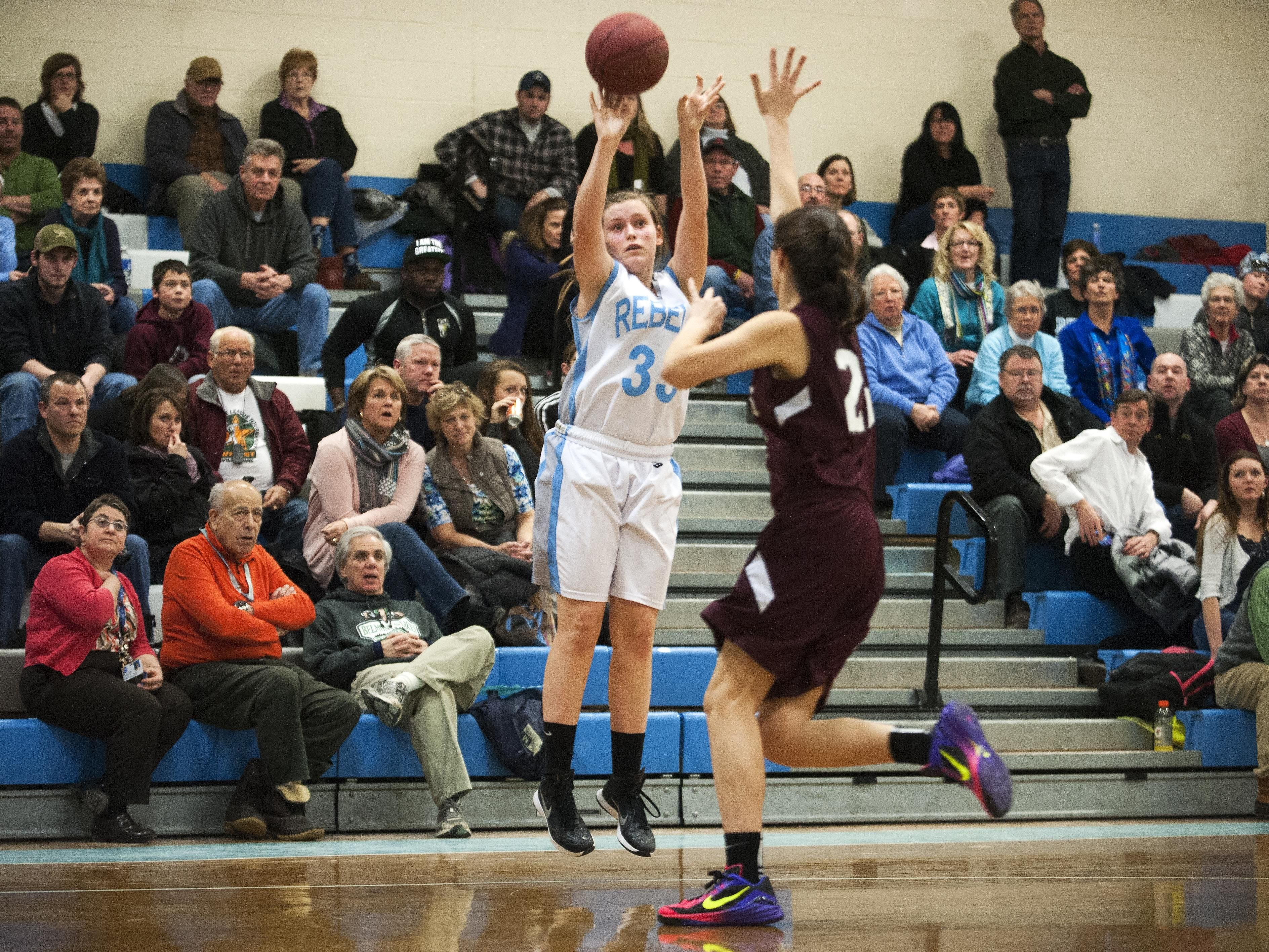 South Burlington's Emma MacDonough (33) takes a 3-point shot during a high school girls basketball game last year.