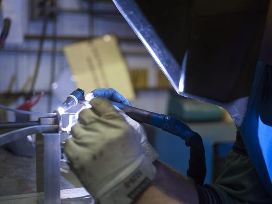 A welder working on a project at Hubbardton Forge.