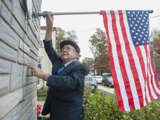 96-year-old veteran Salvatore C. DeSanto raises the American flag outside his home in Oaklyn. DeSanto was laid off from his part-time job this year after 31 years and he wants to find another part-time but is having difficulty getting one because of his age.