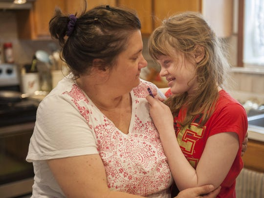 Medical marijuana patient Genny Barbour, who is autistic and suffers from seizures, hugs her mother, Lora, at their home in Maple Shade, N.J. The 16-year-old fought to be able to use her medicine at school.