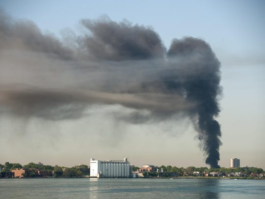 As seen from the MacArthur (Belle Isle) Bridge, a column of smoke billows into the sky from a fire Monday morning at a mixed-use building in the 800 block of Wyandotte in Windsor, directly across the Detroit River from downtown Detroit. The building houses a restaurant and an auto shop.