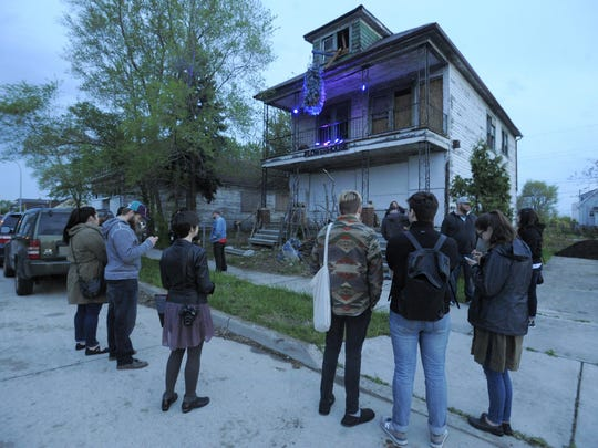 People stand outside the Flower House, Monday May 16, 2016, as deconstruction will begin soon at the home located on Dequindre in Hamtramck. (Steve Perez/ The Detroit News)