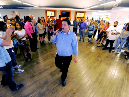 David Poppe, a engagement specialist at United Shore, leads a group of employees in a dance break. Employees take turns deejaying their playlists.