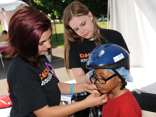 "Livonia's ""Passport to Safety"" offered free bike helmets as Kohl's voulteers Izabella Bowles and Hannah Kero fit Devin Robinson with a new bike helmet."