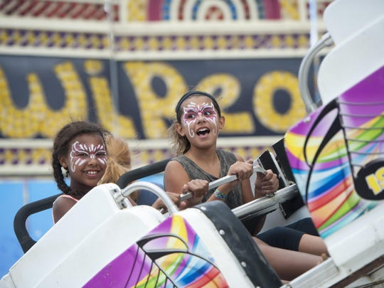 Twelve-year-olds Elise Joshua, left, and Gianna Rodriguez ride the Wipeout Thursday at the Michigan State Fair at the Suburban Collection Showplace in Novi. Even urban areas are feeling tourism love, officials say.