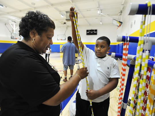 "Physical Education Teacher Ann Turner, left, and Elijah Blue, 10, a fifth-grader, organize jump ropes. The gym received a makeover courtesy of the TV show ""Ellen"" and Lowe's."