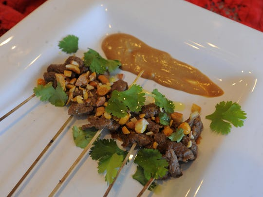 The Asian Beef Satay dish with Hoisin Peanut Sauce involves marinating flank steak before threading the meat on bamboo skewers.