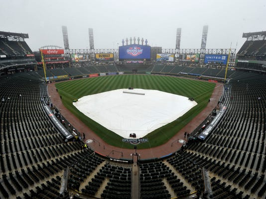 A rain tarp covers the field at Guaranteed Rate Field during a rain delay on opening day before an MLB baseball game between the Chicago White Sox and Detroit Tigers, Monday, April 3, 2017 in Chicago. (AP Photo/Paul Beaty)