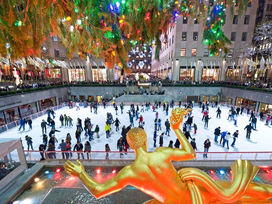 Skaters glide past the statue of Prometheus at Rockefeller