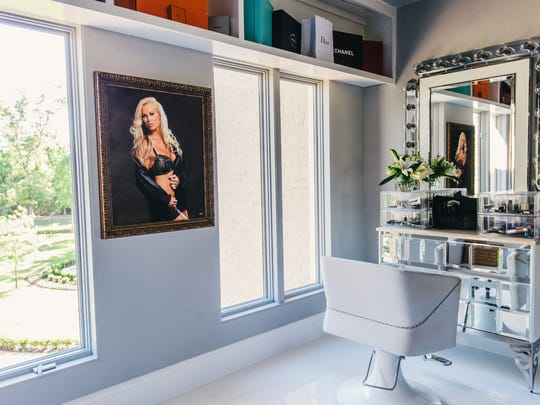 Theresa Roemer, depicted in the boudoir-style portrait on the wall, can apply her makeup in this sunny corner of her mega-closet.