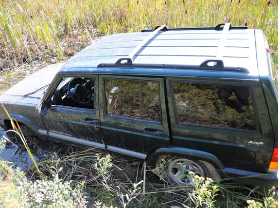 This undated photo provided by the Pennsylvania State Police shows a Jeep that ambush suspect Eric Frein is believed to have driven into a swampy area and abandoned after the Sept. 12 shooting in Blooming Grove, Pa. Frein, a suspect in the fatal ambush of a trooper has occasionally made himself visible to officers before melting back into the forest, and police found empty packs of Serbian-branded cigarettes and soiled diapers believed to have been left by him, Pennsylvania State Police said Wednesday, Sept. 24, 2014.