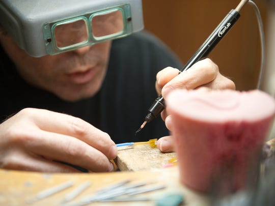 An employee prepares a resin ring mold for casting