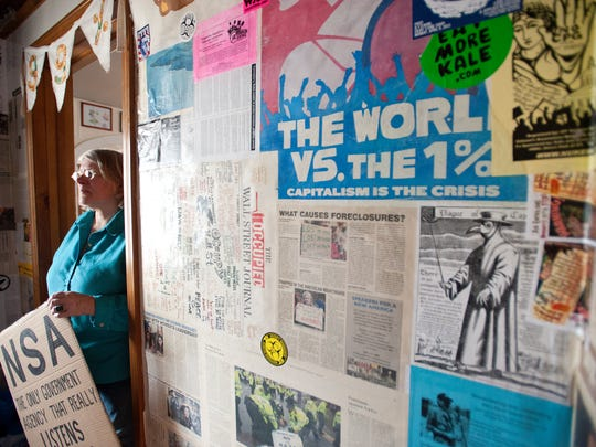 Crystal Zevon of Barre stands in the front hall of her home which is papered with posters, newspaper clippings and remnants of her activist travels.