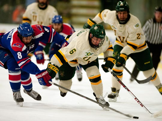 Catamounts forward Colin Markison, right, battles for the puck during a game last season at Gutteron Fieldhouse.