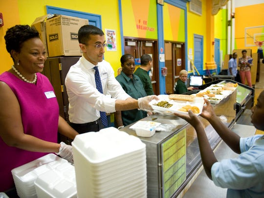 Paymon Rouhanifard (right), Camden's new superintendent of schools, and Mayor Dana Redd serve lunch to students at Cramer Family School on Monday during Rouhanifard's tour there.  JOHN ZIOMEK/Courier-Post Camden School Superintendent Paymon Rouhanifard and Mayor Dana Redd serve lunches to students at Cramer Family School. Monday, September 9, 2013.