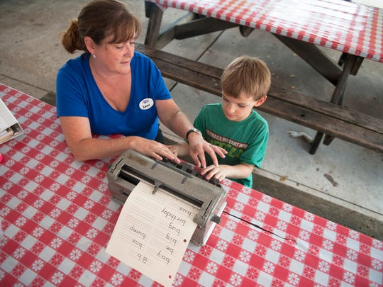 Henry Norton, 6 of Mount Laurel,  who was born deaf and is now nearly blind from a rare genetic disease called Usher syndrome, is assisted by deafblind intervener Lauri Wendel as Norton practices using a braille writer to spell words at Liberty Lake Day Camp in Bordentown.  08.13.14