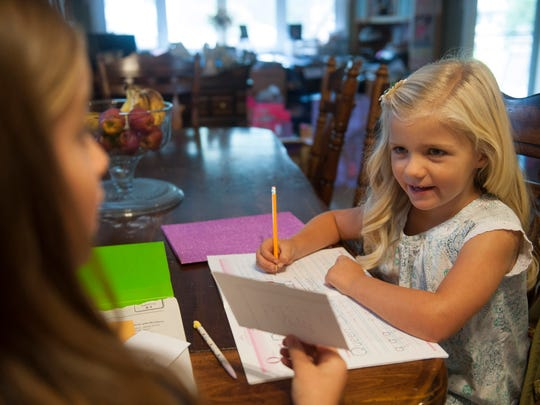 Julia McLaughlin, (left) helps her sister Tristyn with homework. The McLaughlin children missed several days of school last year when their family went on vacation, and they struggled to keep up with school work.
