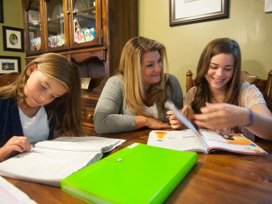 Sherrie McLaughlin helps her daughters (left) Julia 9, and Ryleigh 13, with homework. For story about kids missing school for family trips. Thursday, September 25, 2014.