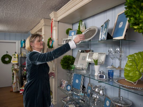 Karen Yang, owner of Refined on Main home decor, organizes a display at her shop in Medford.