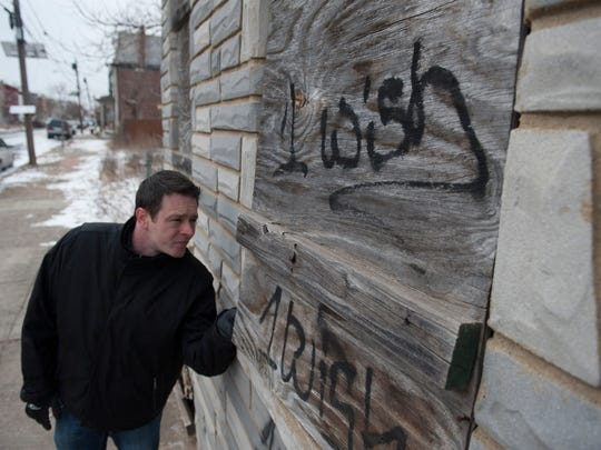 Patrick Duff looks through a boarded up window of the house on Walnut St. in Camden where Martin Luther King Jr. lived when he was a seminary student in Chester, PA. Monday, February 16, 2015.