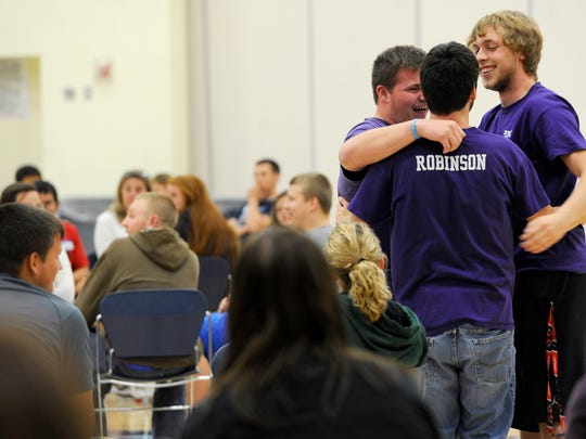 """Adena High School students, Lucas Ramsey, left, and Ben Hooks, right, hug a classmate during an apology session of the """"Respect Everyone Despite Odds"""" retreat at Adena High School on Wednesday. Students and faculty took the moment to apologize to their colleagues for past transgressions and were, in this case, forgiven with a hug and a smile."""
