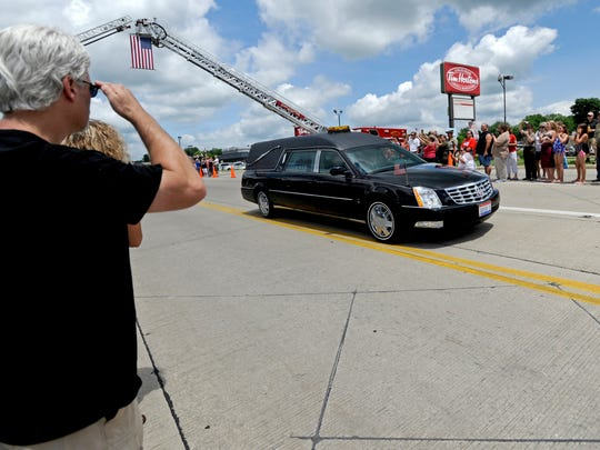 Residents and supporters lined the streets along U.S. 23 in Waverly on June 21 to pay their respects and show their support as the body of Spc. Justin Helton was brought home. Retired Air Force member Rob Crabtree, left, of Waverly, salutes as the hearse carrying Helton drives through town. Gazette online readers narrowly voted Helton's tragic story as the biggest local news story of 2014.