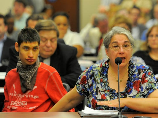 Celeste Chippero of West Bloomfield speaks during the Oakland County Community Health Authority meeting with her son, Peter, beside her.