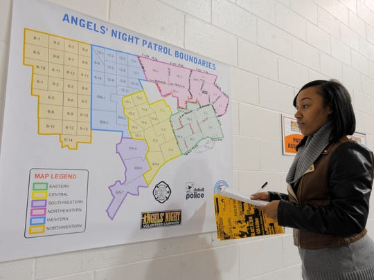 Joya James of Detroit checks out a map for the area she will patrol, Wednesday at the Butzel Family Center on Detroit's east side.