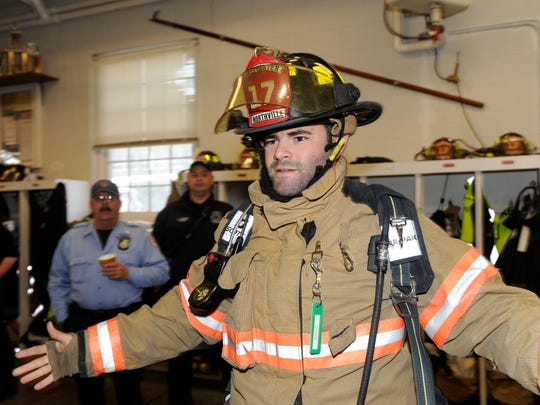Detroit Tigers catcher Alex Avila dons his firefighting gear at the Northville City Fire Department Friday in Northville.