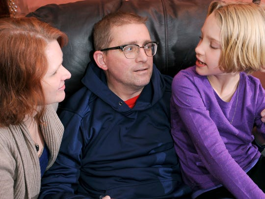 Sara and Jason Gooley spend some time with their daughter Madeline, 9, at their home earlier this month.