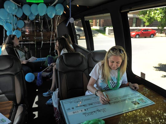 Sarah Sperling of The Community Foundation of Middle Tennessee writes honorary checks with others in The Big Payback party bus, which drove around the area Tuesday giving money to nonprofits. The awards were based on the fundraising performance of the nonprofits as part of the inaugural giving campaign on Tuesday May 6, 2014, in Nashville, Tenn.