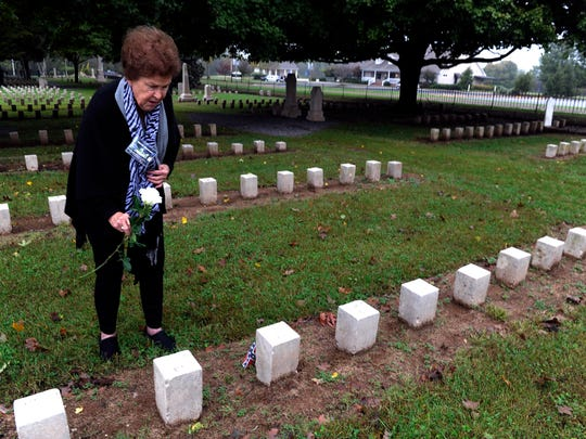 Gloria Ramsaur places a rose at the gravesite of her great-great-uncle, William G. Hightower, at McGavock Confederate Cemetery during a Civil War descendants reunion last month. Ramsaur, an avid family historian, learned from a handwritten family tree that Hightower was killed at the Battle of Franklin in 1864.