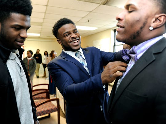 Pearl-Cohn football player Ke'Shawn Vaughn helps fellow player Joshua Montgomery put on his tie before a signing day ceremony at the school on Feb. 4, 2015.