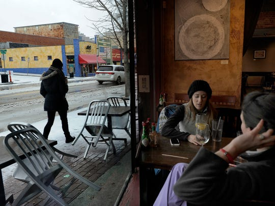 Vanderbilt nurses Megan Garcia and Jillian Witzke have drinks as a person walks by at Fido in Hillsboro Village. Ice and sleet covered the streets in Nashville.