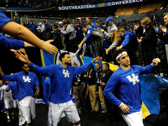 Kentucky players slap hands with fans as they take the court before their game against Auburn on Saturday.