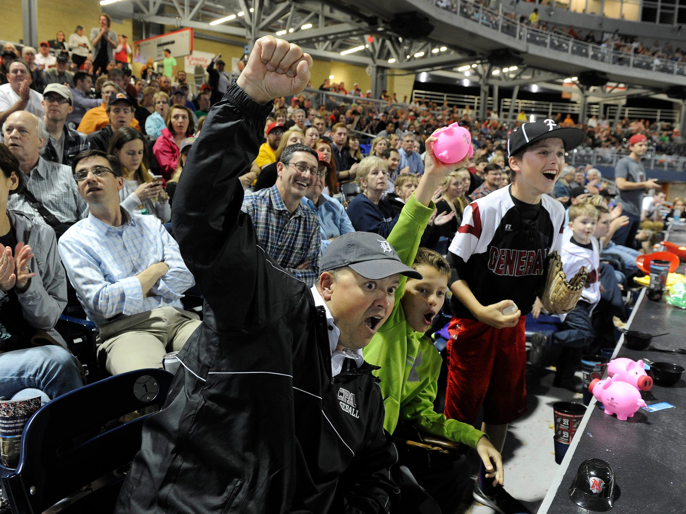 Fans Todd Sweat and sons Owen and Ford get excited in the bottom of the ninth at First Tennessee Park Friday.