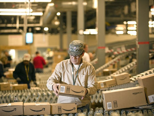 An Amazon.com employee grabs boxes off the conveyor belt to load in a truck at its Fernley warehouse in December 2008.