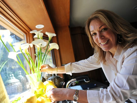 "In her kitchen window, Araceli Bernardasci rearranges Calla lilies given to her by her husband, David. He's her caretaker, cheerleader and inspiration in her battle against cancer. ""I consider myself a warrior and my husband my No. 1 soldier,"" she said."
