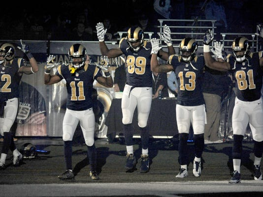 FILE - In this Sunday Nov. 30, 2014, file photo, St. Louis Rams players, from left; Stedman Bailey (12), Tavon Austin (11), Jared Cook, (89) Chris Givens (13) and Kenny Britt (81) raise their arms in awareness of the events in Ferguson, Mo.,  as they walk onto the field during introductions before an NFL football game against the Oakland Raiders in St. Louis. Time will tell whether the ``hands-up'' gesture during pregame introductions will leave a lasting memory or simply go down as a come-and-go moment in the age of the 24-hour news cycle. Either way, it certainly isn't the first time high-profile athletes have used their platform to make political statements. (AP Photo/L.G. Patterson, File)