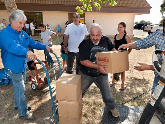 Steve Dresser, left, steadies a dolly as Ralph Renteria and Mark Prieto unload some of the 660 boxes of food distributed by Foodlink.