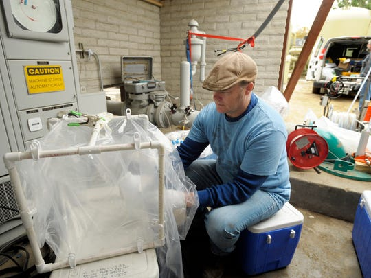 Greg Smith, pictured, with the U.S. Geological Survey, takes a sample of well water to test.