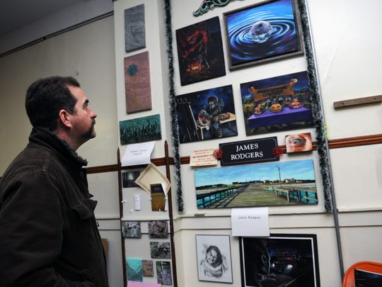 Gregory Smith, an auctioneer, admires artwork by James Rodgers on display Jan. 2 at the Artist Collective inside the Masonic Temple during the First Friday Art Walk in Zanesville. Eighteen studios and galleries and 14 businesses participated in the event.