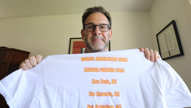 Andrew Friedman author of Chefs, Drugs & Rock & Roll, at his Hastings-on-Hudson home April 23, 2018. He is holding a shirt he made commemorating his book promotion tour.