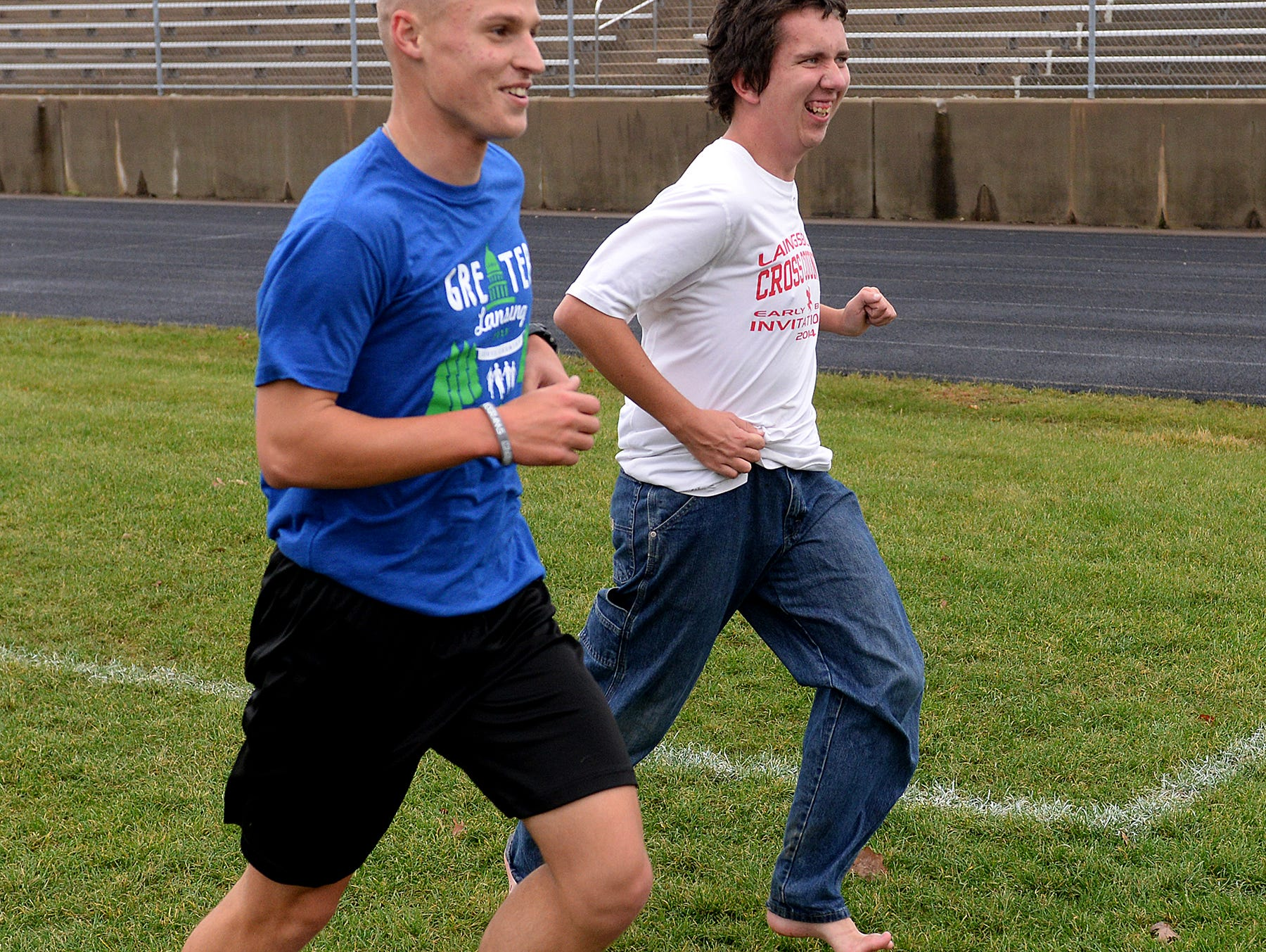 """Sophomore Ryan Kingsbury, in blue, runs with Ray Latchaw to encourage him to finish out his last run during a Laingsburg cross country team practice Wednesday, October 28, 2015 at Laingsburg High School. Latchaw, a junior, is autistic, but runs, he says, to stay healthy and because he enjoys the """"me time"""" he gets."""