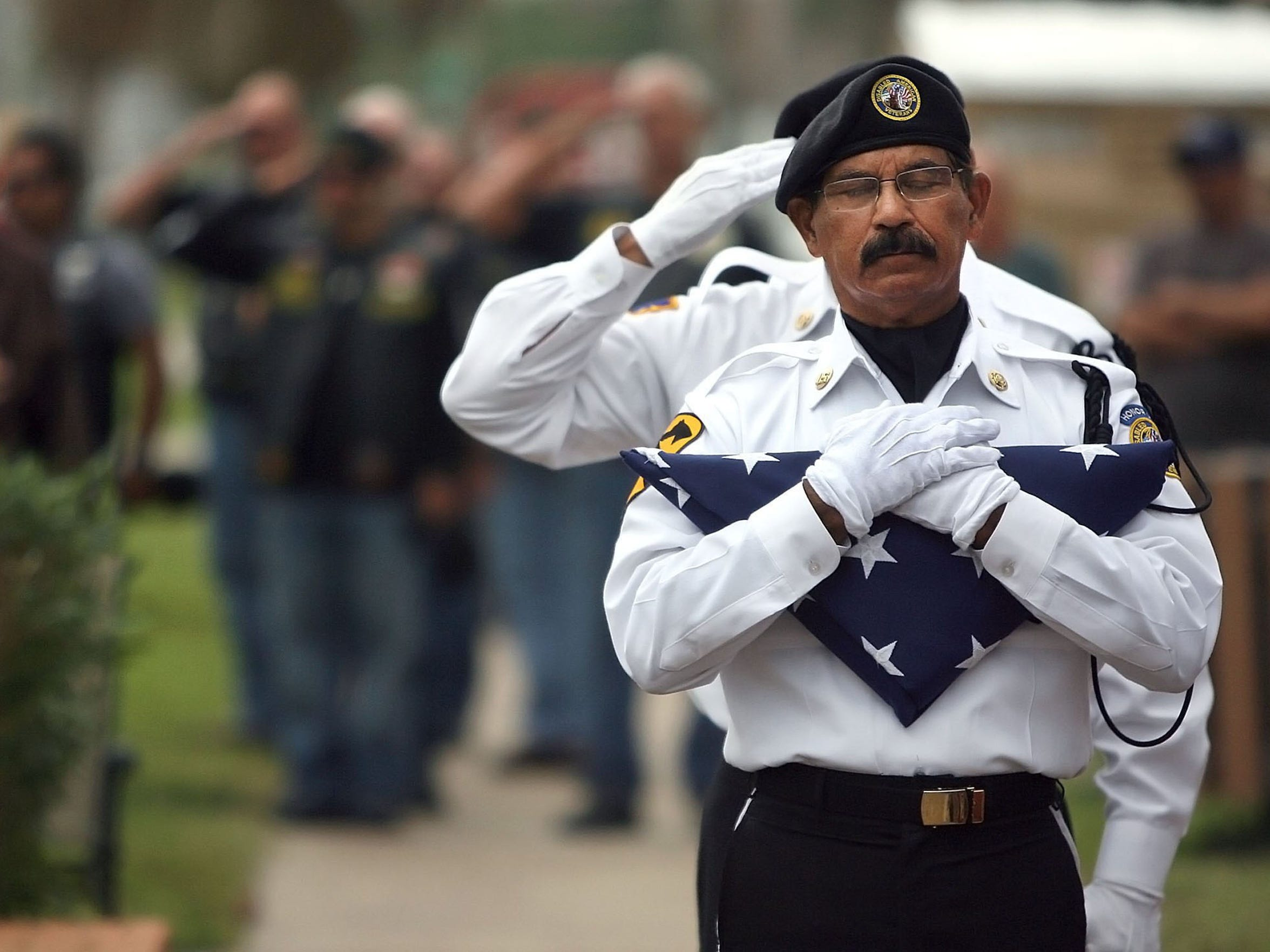 Todd Yates/Caller-TimesTony Acevedo, member of the Veterans Band of Corpus Christi Color Guard, cradles the American flag as Taps is played during Veterans Day ceremony at Sherrill Park in 2014.
