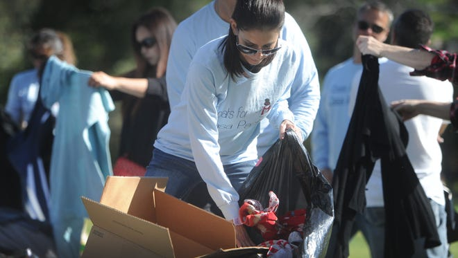 Michelle Scruggs, volunteer sorts through some jackets and coats at the Coats for Casa at Three Springs Park in Westlake Village. This was the 7th annual event for a worthy cause by dropping off a gentle used warm clothing item.